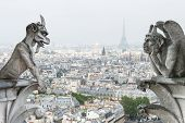 stock photo of notre dame  - Stone demons gargoyle und chimera with Paris city on background - JPG