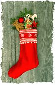 stock photo of nostalgic  - christmas stocking with nostalgic antique toy decoration and pine branch over wooden background - JPG