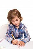 pic of homework  - Student boy writing for homework at his desk - JPG