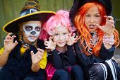 pic of repentance  - Portrait of three little girls in Halloween costumes looking at camera with frightening gesture - JPG