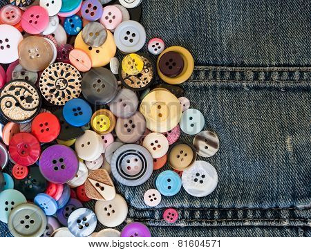 sewing buttons on denim jeans background