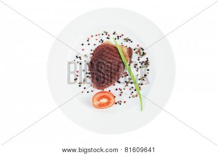 savory : grilled juicy beef pork steak served with red tomato allspice pepper green chives on plate isolated over white background
