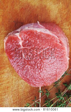 raw red meat : fresh beef single fillet chop with thyme on wooden plate . isolated over white background