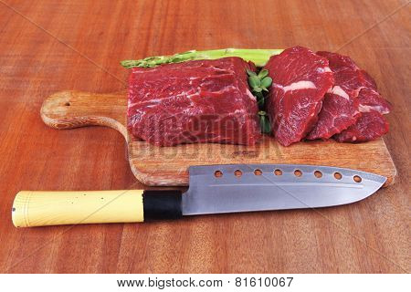 red fresh raw beef veal fillet with asparagus and stainless steel chef knife on cutting plate over wooden table prepared to use