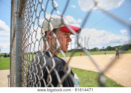 Teen boy on sidelines at baseball practice