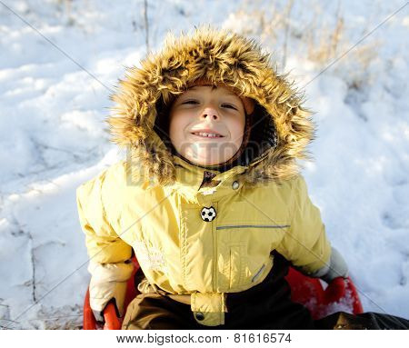 little cute boy in hood with fur on snow outside