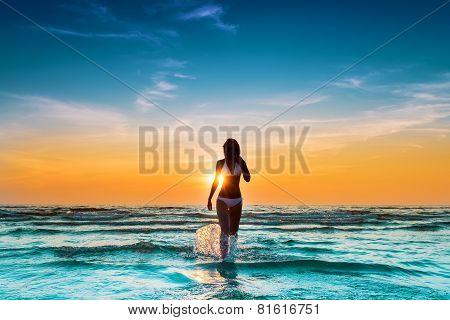 woman in white bikini posing in a sea at sunset