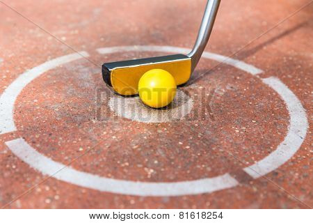 Miniature golf club with ball at round