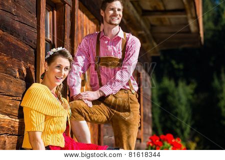 Couple in traditional clothing front of mountain hut marveling at the scenery