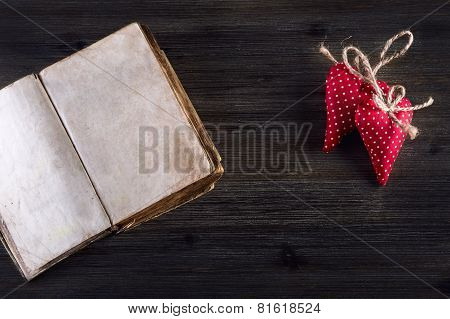Valentines day. Red cloth handmade hearts and old open book on wooden background