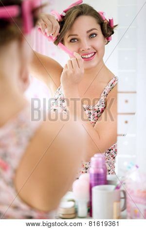 smiling young girl putting curlers in hair