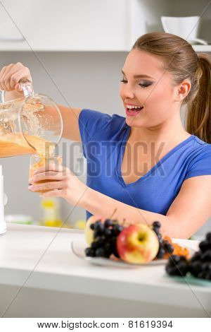 Smiling young woman holding a blender with a fruit smoothie and pouring it into a glass