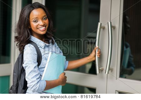 smiling african female college student going to lecture hall