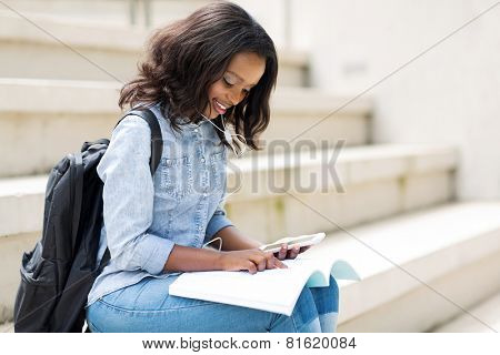 pretty young afro american college girl reading on campus