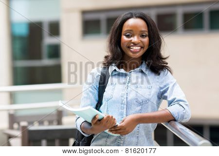 happy afro american college student holding a book