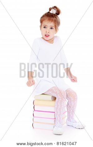 little girl froze while sitting on a stack of books.