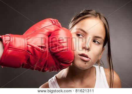 little girl and red boxing globe  hitting her face