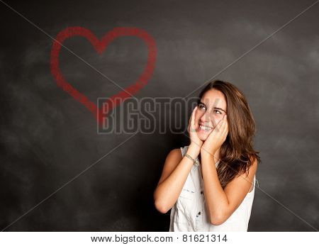 portrait of young girl thinking in front of chalkboard
