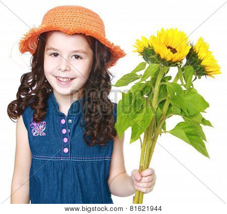 Beautiful little girl in a hat and holding flowers.