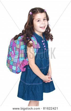 Beautiful little schoolgirl with a knapsack on his shoulders.