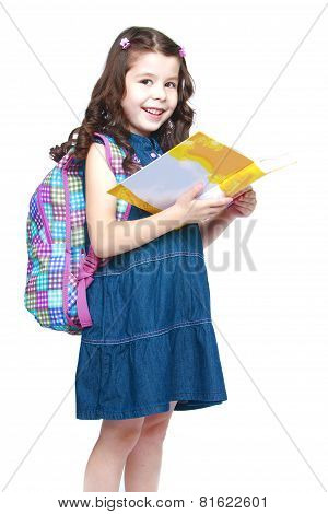 Happy little schoolgirl with backpack reading a book.