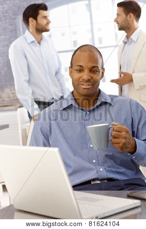 Closeup portrait of young black businessman sitting at desk, using laptop computer, drinking tea, working.