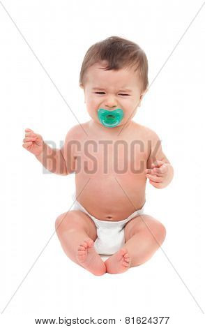 Sad six month baby in diaper lying on the floor isolated on white background