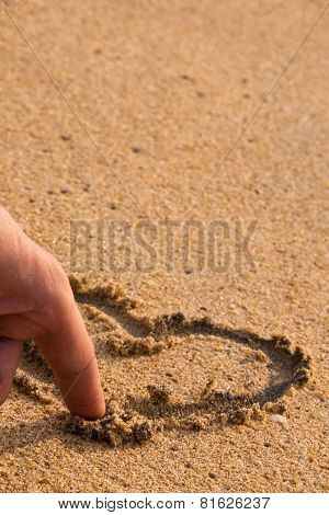 Finger Draws A Love Heart In The Sand