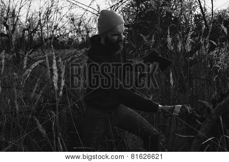 bearded lumberjack is chopping stump