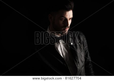 Close up pictue of a handsome business man looking away from the camera on dark studio background.