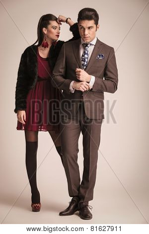 Full body picture of a young fashion couple posing on studio background. She is leaning on his shoulder while he is fixing his shirt.