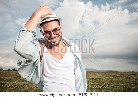 Smiling young fashion man holding his hat while looking down, posing on a field full of flowers.