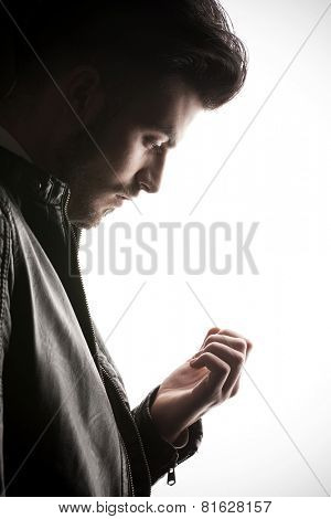 Side view picture of a young casual business man looking down at his fingers.