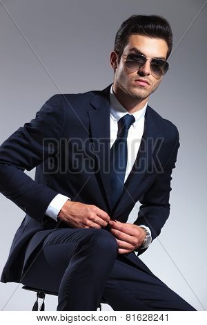 Handsome business man sitting while closing his jacket, looking away from the camera.
