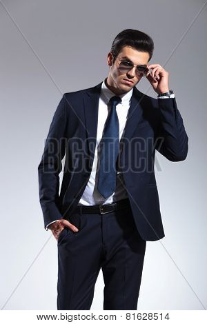 Young elegant business man taking off his sunglasses while holding one hand in his pocket.