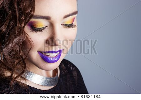 fashion beauty shot of a beautiful young sexy girls with bright makeup and purple lips in the Studio