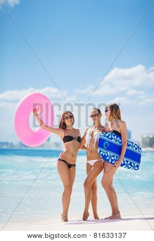 Three slim woman in bikini with a lifeline, having fun near the ocean.