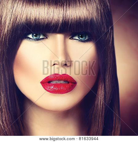 Beautiful brunette woman with fashion fringe haircut and professional makeup. Red lips, smooth brown hair