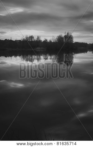 Black And White Of A Mountain Lake Under Partly Cloudy Sky' With Lily Pads On The Lakes Surface And