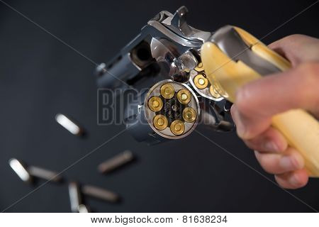 A pistol with bullets on a black background.