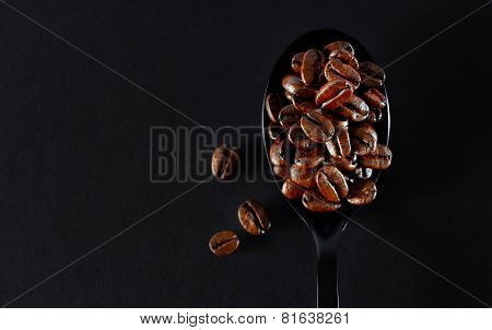 Roasted Coffee Beans On Black Spoon