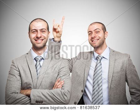 Funny businessman making the horns sign to himself