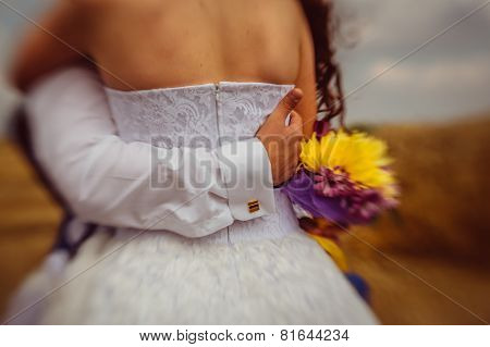 Closeup Of A Groom's Arm Holding His Bride's Back