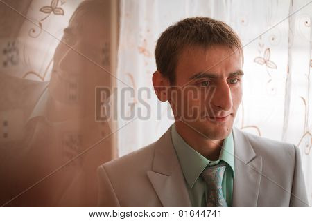 Portrait Of Young Groom Tying Tie While Getting Ready For Wedding