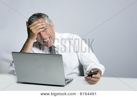 Laughing Senior Businessman Computer Phone Gesture
