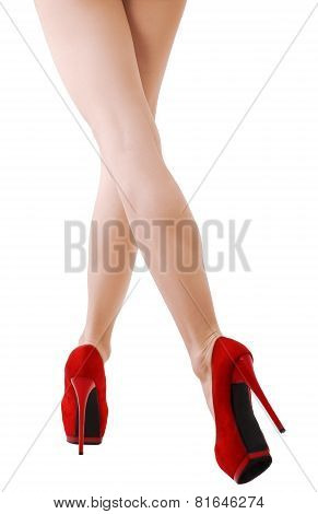 Sexy woman legs in motion at red suede shoes