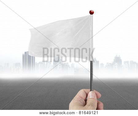 Hand Holding Blank White Flag With Gary Cityscape
