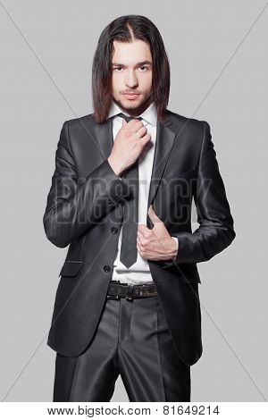 stylish man with long hair in elegant black suit