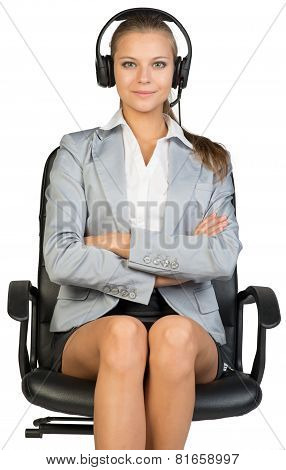 Businesswoman in headset sitting on office chair, her arms crossed