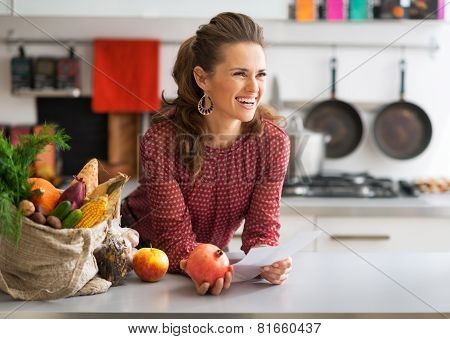 Happy Young Housewife Holding Grocery Shopping Checks In Kitchen